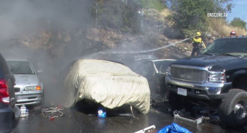 Lakeside Fire Protection District firefighters work to extinguish the flames of a small brush fire that destroyed two vehicles and threatened homes Wednesday afternoon.