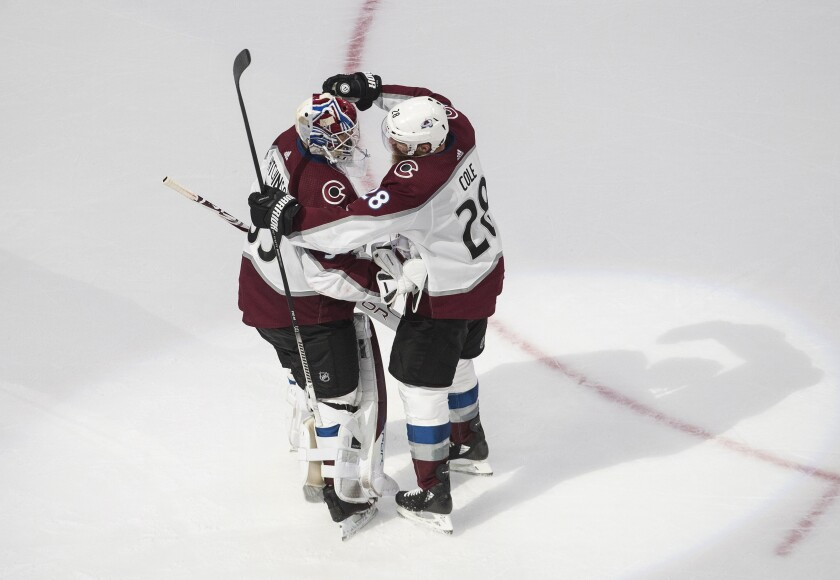 Colorado Avalanche goaltender Michael Hutchinson (35) and teammate Ian Cole (28) celebrate the Avalanche's win over the Dallas Stars in Game 6 of an NHL hockey second-round playoff series, Wednesday, Sept. 2, 2020, in Edmonton, Alberta. (Jason Franson/The Canadian Press via AP)