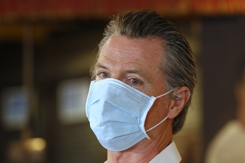 California Gov. Gavin Newsom, wears a face mask as he answers a reporter's question.
