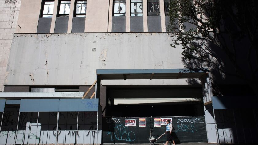 LOS ANGELES, CA-JANUARY 23, 2019: A woman walks past the exterior of an unoccupied 13-story building
