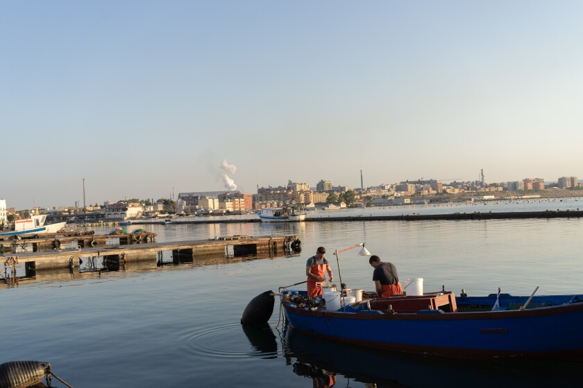 Two fishermen clean their catch in old Taranto's harbor. On the horizon is a column of vapors from ArcelorMittal's steel plant.