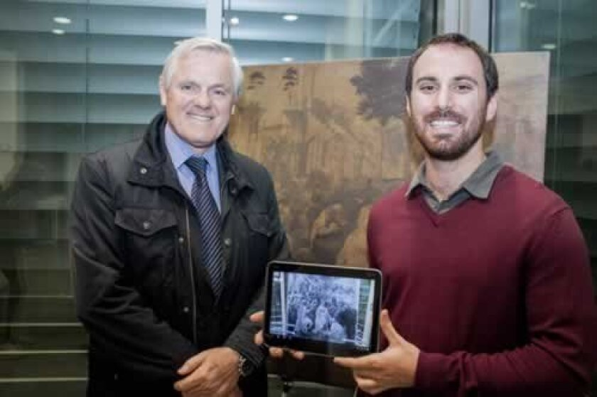 At 'Corpus,' a faculty art exhibition, Maurizio Seracini and David Vanoni pose with their new tablet app, which reveals what lies beneath a classic painting. Maurice Hewitt