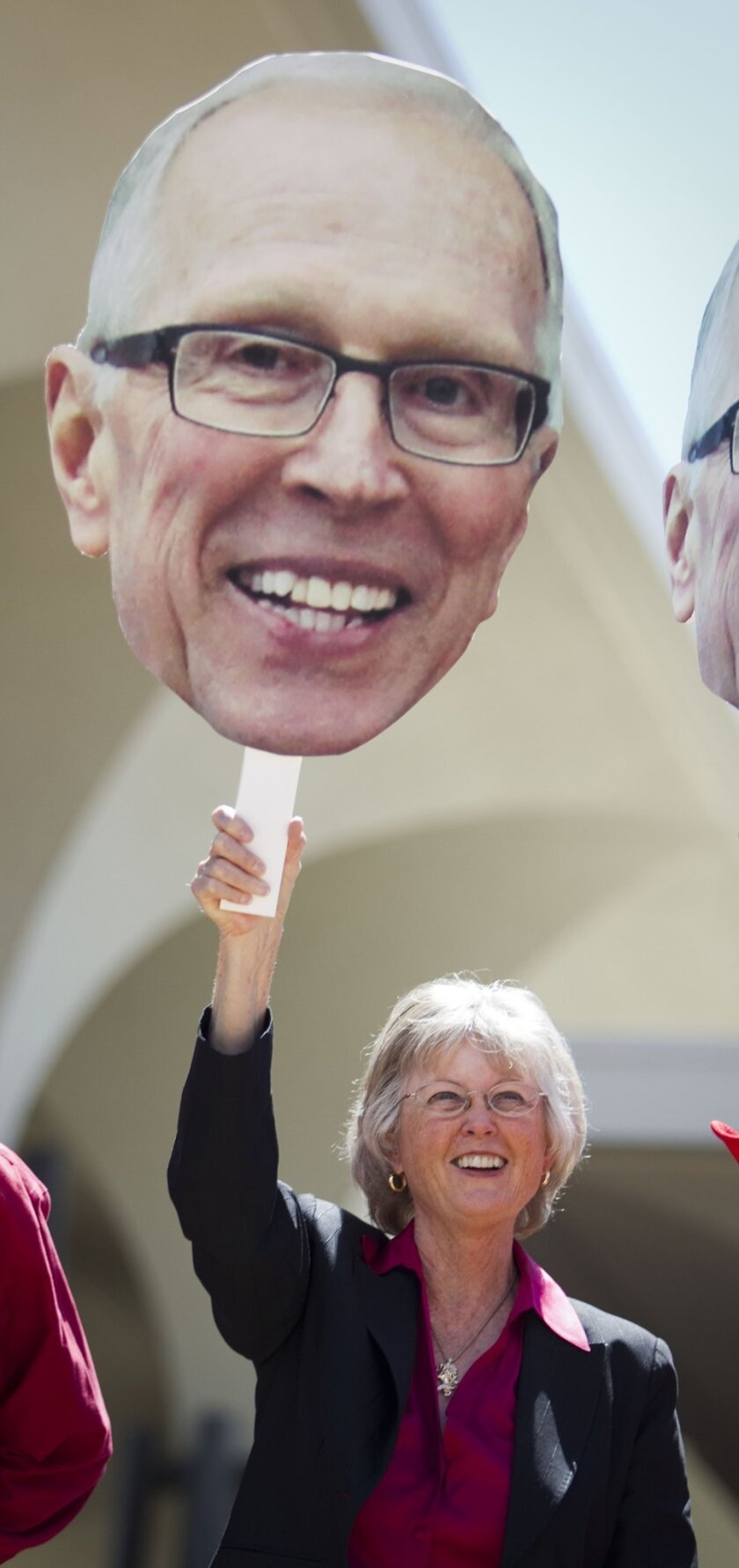 SDSU grad and sports fan Dianne Jacob waves a Steve Fisher sign at a celebration for the Aztecs season in 2011.