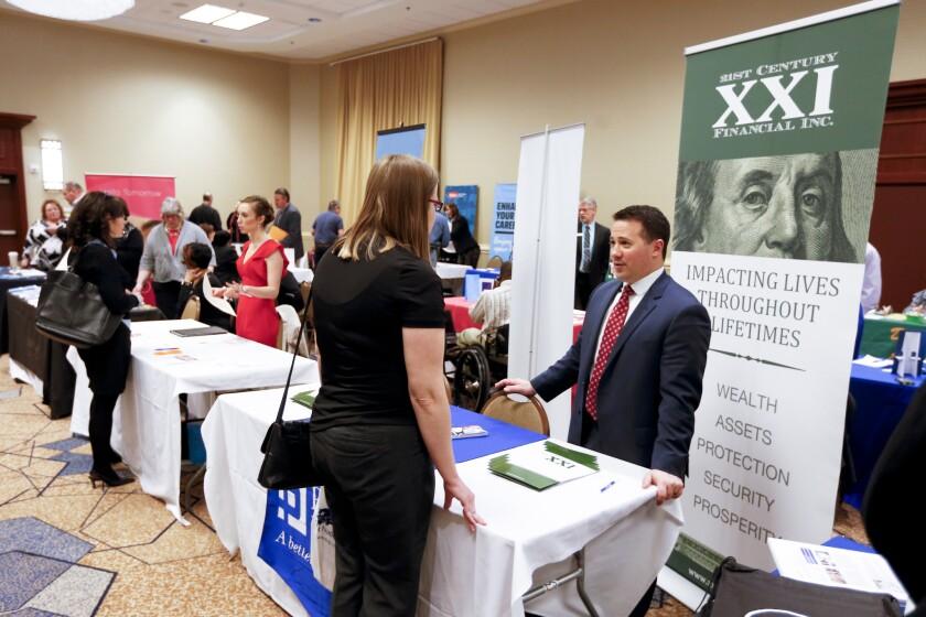 Companies speak with job seekers at a job fair in Pittsburgh.