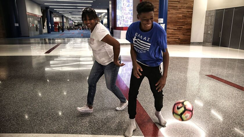 Yvonne Ferguson-Smith and her son, Travis, play in the halls of the George R. Brown Convention Cente