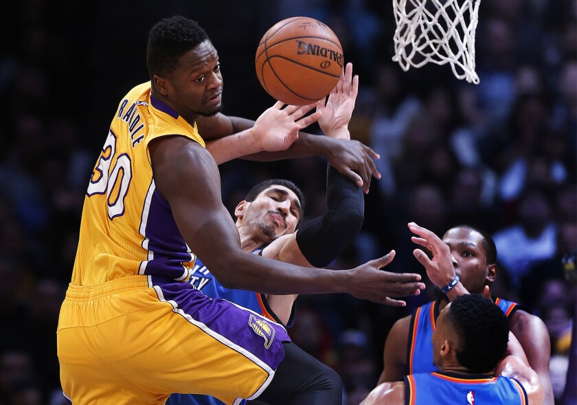 Lakers forward Julius Randle, left, collides with Thunder center Enes Kanter while going for a rebound late in the game.