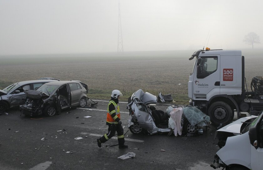 A firefighter walks past the wreckage of some cars on the A19 highway in Zonnebeke, western Belgium, Tuesday, Dec.3, 2013. Dozens of cars and trucks crashed in dense morning fog, killing at least one and injuring dozens more. (AP Photo/Yves Logghe)
