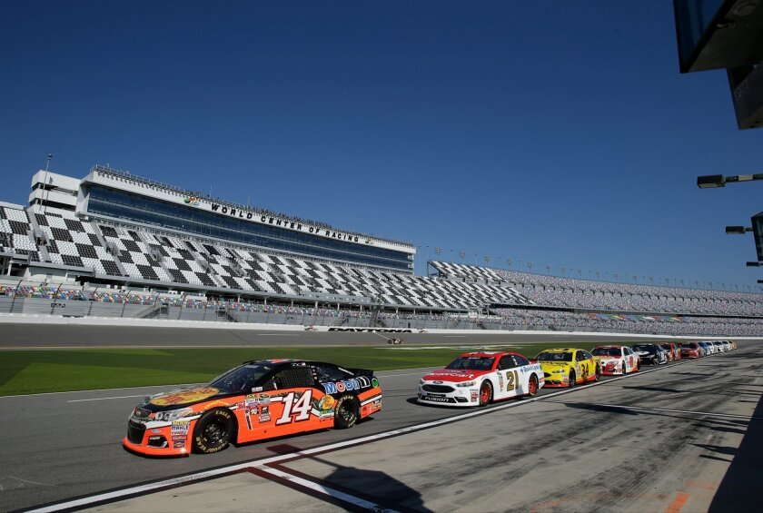 Drivers, including Brian Vickers (14) and Ryan Blaney (21),  line up on pit road waiting to go out on the track during a practice session for the NASCAR Daytona 500 auto race at Daytona International Speedway, Saturday, Feb. 13, 2016, in Daytona Beach, Fla. (AP Photo/John Raoux)