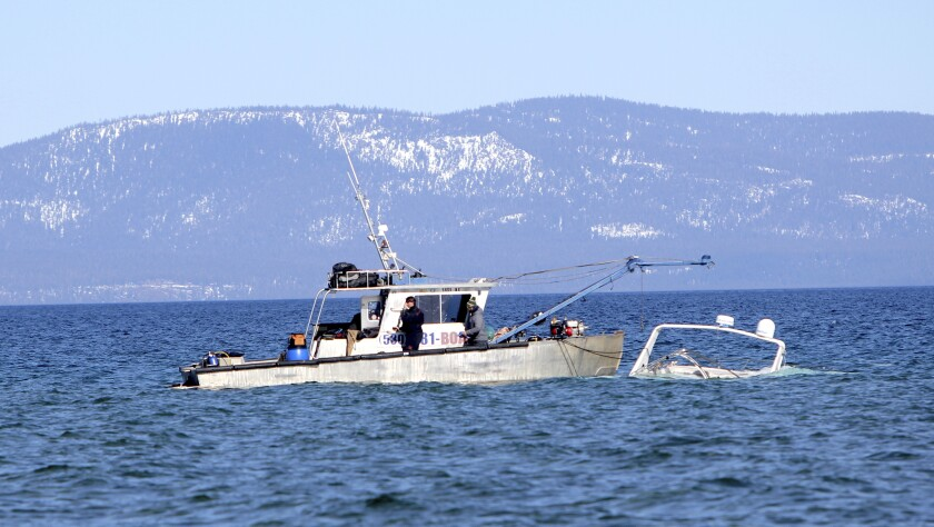 A crew for High Sierra Marine Inc. recovers a sunk boat , Tuesday, Feb. 23, 2021, of the shore of South Lake Tahoe, Calif. The boat sunk in January and had been leaking oil. The U.S. Environmental Protection Agency hired the contractor to raise the abandoned 40-foot recreational vessel in coordination with the El Dorado County Sheriff, the Lahontan Regional Water Quality Control Board, Tahoe Regional Planning Agency and the California Department of Fish and Wildlife Office of Spill Prevention and Response. (Bill Rozak/The Tahoe Tribune via AP)