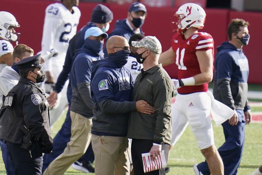 Nebraska head coach Scott Frost, right, meets with Penn State head coach James Franklin, following an NCAA college football game in Lincoln, Neb., Saturday, Nov. 14, 2020. Nebraska won 30-23. (AP Photo/Nati Harnik)