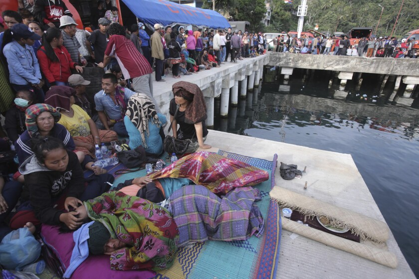 Relatives of victims of a sunken ferry wait for news at the Tigaras port in Toba lake, North Sumatra