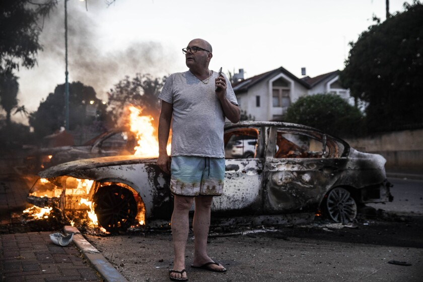 Jacob Simona stands by his burning car in Lod, Israel.