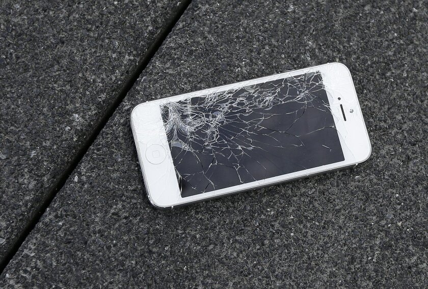 This Aug. 26, 2015 photo shows an Apple iPhone with a cracked screen after a drop test from the DropBot, a robot used to measure the sustainability of a phone to dropping, at the offices of SquareTrade in San Francisco. Despite engineering breakthroughs, screen breakage has become a part of life, the leading type of phone damage. (AP Photo/Ben Margot)