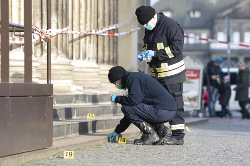 Police officers work behind a caution tape at the Schinkelwache building in Dresden