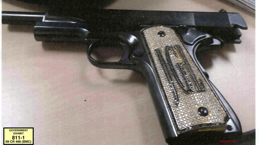This undated photo provided by the U.S. Attorney's Office shows a diamond-encrusted pistol that a go