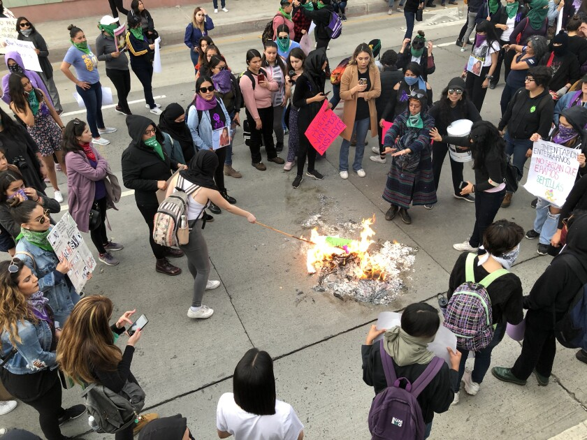 Women protesting murder and violence against women in Mexico burned their signs after a march in Tijuana to the San Ysidro Port of Entry on Feb. 22, 2020.