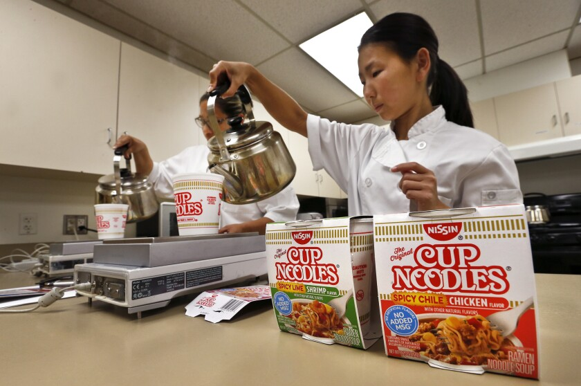 Nissin Foods USA research development assistants Veronica Sanchez, left, and Saori Seki prepare their company's noodle dishes in a Gardena test kitchen.