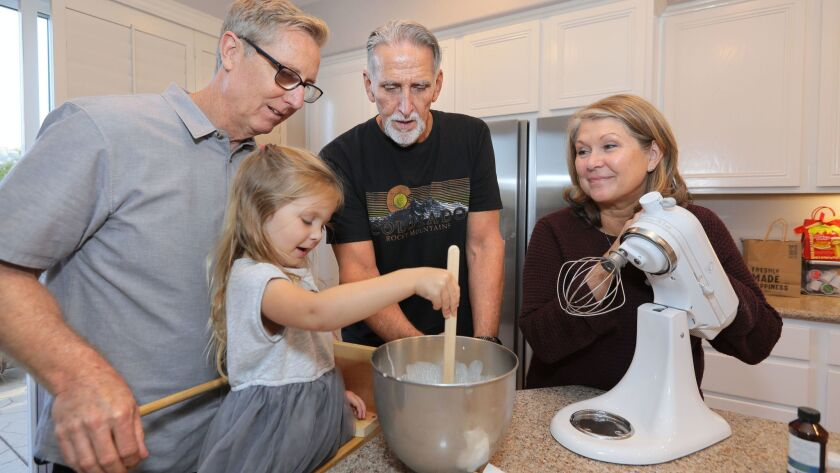 Craig Coley, middle, watches 3 year old Keira Andrew help make whipped cream for Thanksgiving pumpkin pies. With them are Keira's grandparents Mike Bender and his wife Cyndi. Mike's efforts led to C