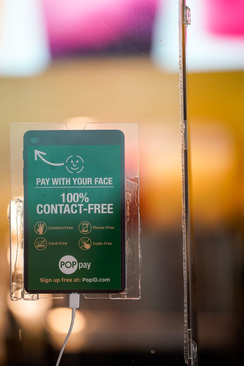 "A tablet mounted on a sneeze guard at a Lemonade restaurant advertises the ""100% contact-free"" Pop Pay system"