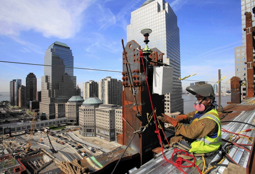 Aecom projects include construction management for the new World Trade Center in New York. Above, a welder works on the project.