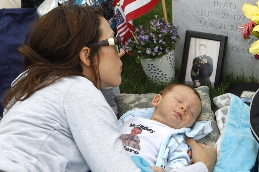 Jenn Budenz lies on a blanket with her 2-month-old son AJ as she looks at a picture of her husband Major Andrew Budenz, who was a Marine C-130 pilot in Iraq and Afghanistan, as she visits her husband's grave at the Miramar National Cemetery in San Diego on Thursday. Budenz visits