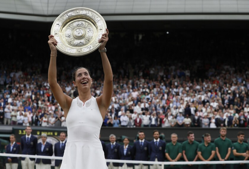 Spain's Garbine Muguruza holds the trophy after defeating Venus Williams in the Women's Singles final match at the Wimbledon Tennis Championships in London on July 15, 2017.