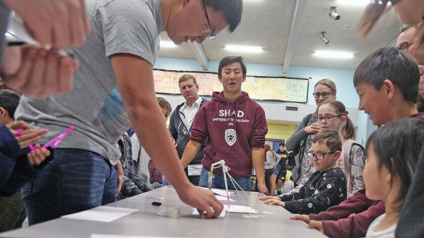 Demonstrating how a seismograph works, La Canada High School students Justin Wang, 16, holds a mock