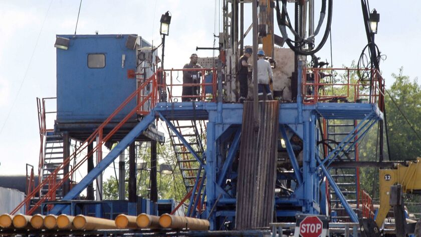 FILE - In this June 25, 2012 file photo, a crew works on a gas drilling rig at a well site for shale