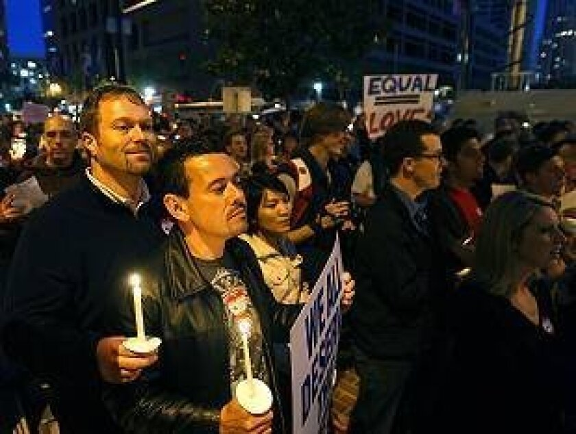 Partners Tyler Jensen, left, and Luis Barrios attend Wednesday's candlelight vigil during a rally against Prop. 8 outside the Hall of Justice. They were married last October.
