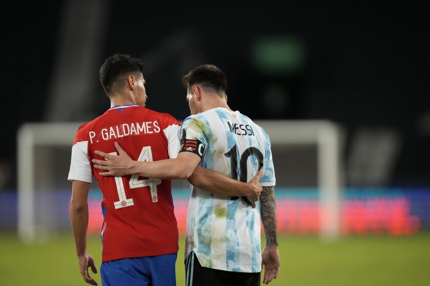 Chile's Pablo Galdames, left, and Argentina's Lionel Messi leave the field after a tie at the end of a Copa America soccer match at the Nilton Santos stadium in Rio de Janeiro, Brazil, Monday, June 14, 2021. The match enede 1-1.(AP Photo/Ricardo Mazalan)