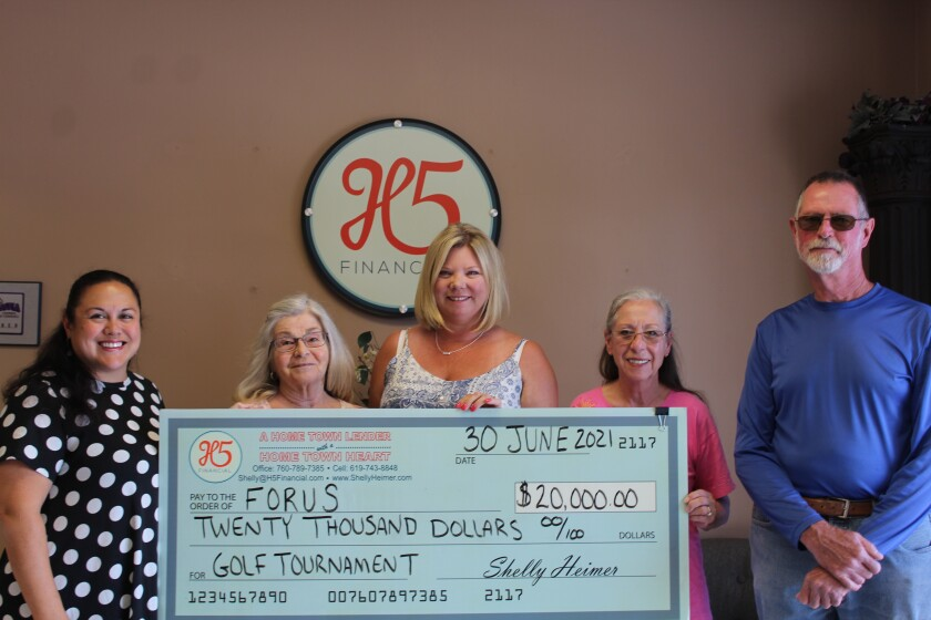 H5 Financial Owner Shelly Heimer, center, presents an oversized check for $20,000 to FORUS members.