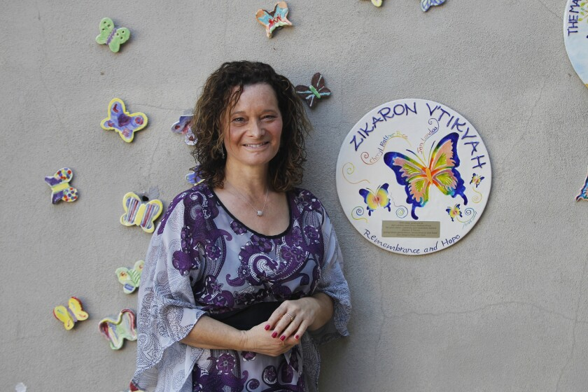 Butterfly Project director Cheryl Rattner Price with a display of hand-painted butterflies at San Diego Jewish Academy