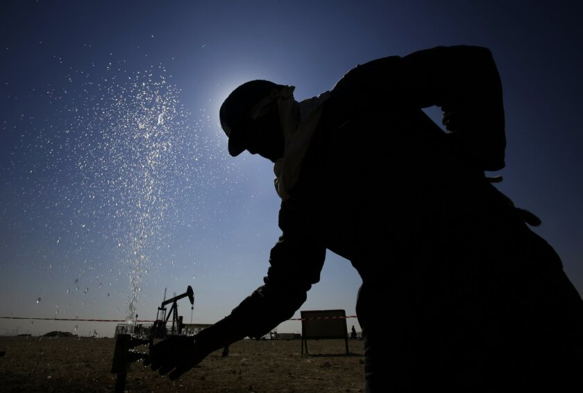 An oil worker adjusts a valve releasing a spray of water while working on oil pipelines Thursday, Feb. 18, 2016, in the desert oil fields of Sakhir, Bahrain. Iran appeared Wednesday to back a plan laid out by four influential oil producers to cap their crude output if others do the same, though it