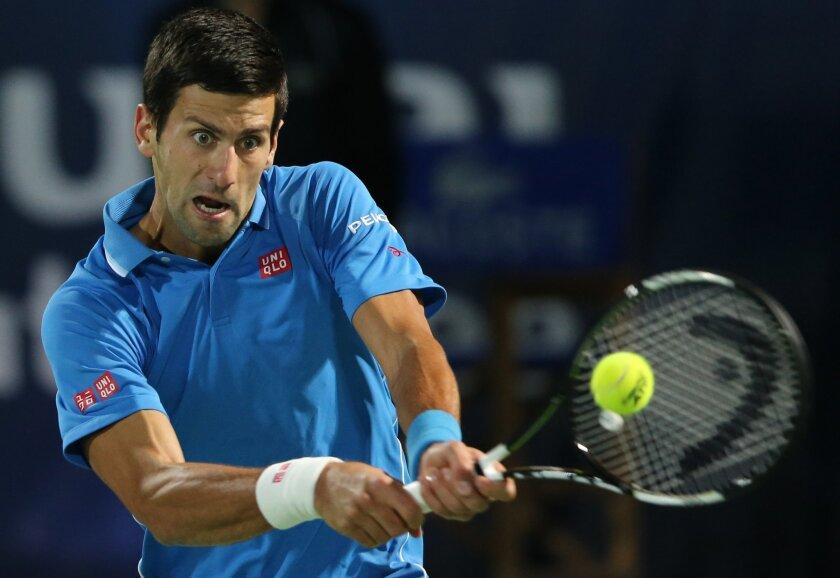 Novak Djokovic of Serbia returns the ball to Roger Federer of Switzerland during the final match of the Dubai Duty Free Tennis Championships in Dubai, United Arab Emirates, Saturday, Feb. 28, 2015. (AP Photo/Kamran Jebreili)
