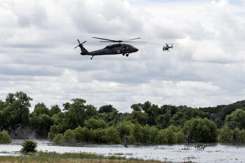 An Army and Texas Department of Public Safety helicopter search Lake Belton Friday, June 3, 2016, for four missing soldiers from U.S Army's Fort Hood that were swept away in a low water crossing during training when the Army vehicle they were in was swept away on Thursday. Five soldiers were killed, four are still missing and three were rescued on Thursday. (Rodolfo Gonzalez/Austin American-Statesman via AP)