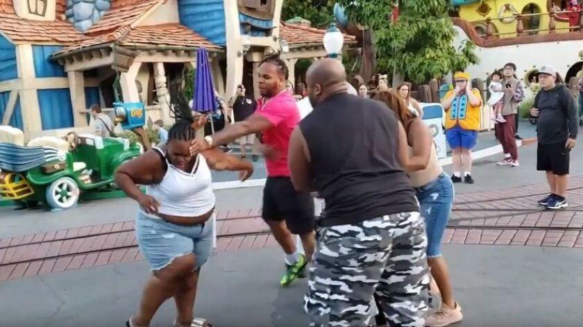Espectadores observan cómo una familia se pelea frente a Goofy's Playhouse en Disneylandia el sábado.