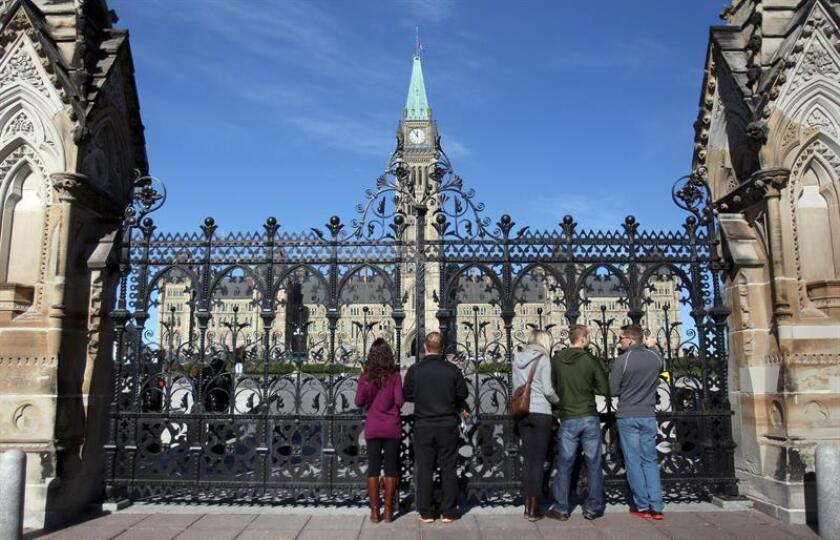 La gente mira al Parlamento desde fuera de las puertas principales en Ottawa, Canadá, el 24 de octubre de 2014. Cpl. EFE/Archivo