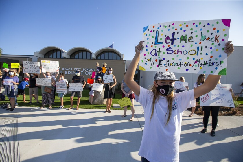 Elliana Emerson, 12, holds a sign during a rally at the Huntington Beach City School District on Tuesday.