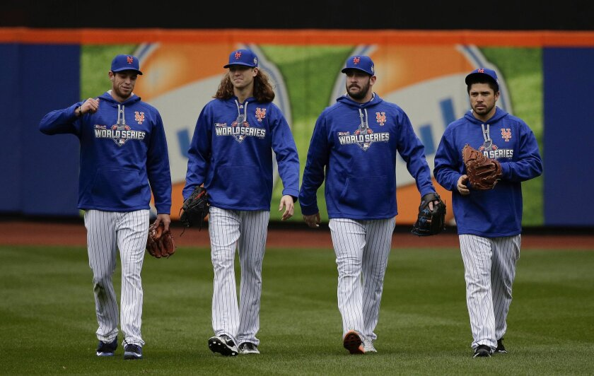 From left, New York Mets pitchers Steven Matz, Jacob deGrom and Matt Harvey and catcher Travis d'Arnaud walk off the field at the end of batting practice, Saturday, Oct. 24, 2015, in New York.  The Mets will face the Kansas City Royals in Game 1 of the World Series on Tuesday. (AP Photo/Julie Jacob