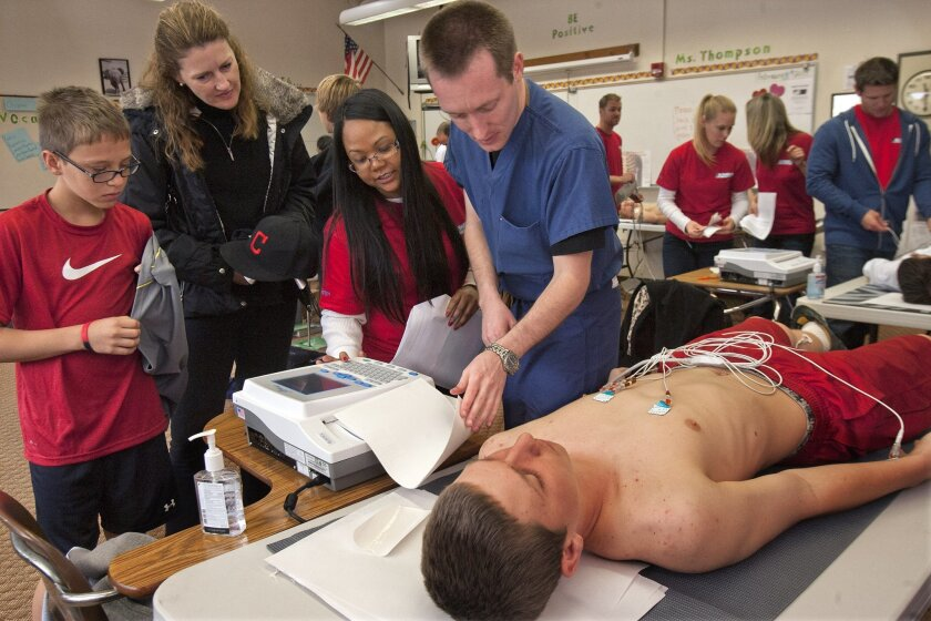 Peter Lutz, 14, is on his back with electrodes that are reading the electrical functions of his heart as his mother Lisa Lutz and his brother William, 12, watch and EKG technician Thay Yin and medical student Timothy O'Brien, both volunteers, conduct an EKG screening during an EKG screening session