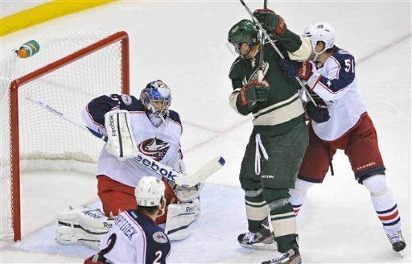 Columbus Blue Jackets' Fedor Tyutin, right, of Russia, keeps Minnesota Wild's Dany Heatley in check as Blue Jackets goalie Curtis Sanford, left, stops a shot in the third period of an NHL hockey game on Saturday, Oct. 8, 2011, in St Paul, Minn. Sanford replaced starting goalie Steve Mason in the third period. The Wild won 4-2. (AP Photo/Jim Mone)