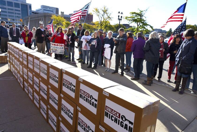 A group gathers as boxes filled with petition signatures are delivered by Unlock Michigan to the Michigan Department of State Bureau of Elections in Lansing, Mich., Friday, Oct. 2, 2020. The Michigan group on Friday submitted at least 539,000 signatures in a bid to repeal a law that has given Gov. Gretchen Whitmer broad emergency powers during the coronavirus pandemic, demanding that the veto-proof initiative be put before the Republican-led Legislature before the year's end. (Rod Sanford/Detroit News via AP)