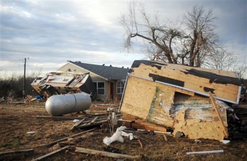 A recreational vehicle leans against a house and a toppled shed sits in the foreground just off Highway E about two miles north of Interstate 44 Friday, Dec. 31, 2010, near Rolla, Mo. Tornadoes fueled by unusually warm air pummeled the South and Midwest on Friday. (AP Photo/Kelley McCall)