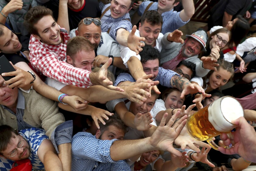 FILE - In this file photo dated Saturday, Sept. 21, 2019, people reach out for a glass of beer during the opening of the 186th 'Oktoberfest' beer festival in Munich, Germany. Bavarian officials have announced Monday May 3, 2021, they have canceled Oktoberfest festivities for the second year in a row due to concerns over the spread of the coronavirus global pandemic. (AP Photo/Matthias Schrader, FILE)