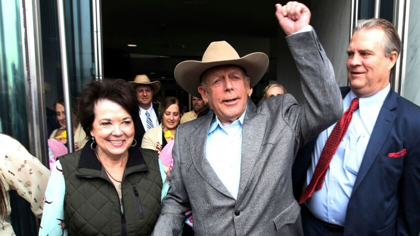 Cliven Bundy walks out of federal court in Las Vegas with his wife Carol on Jan. 8.