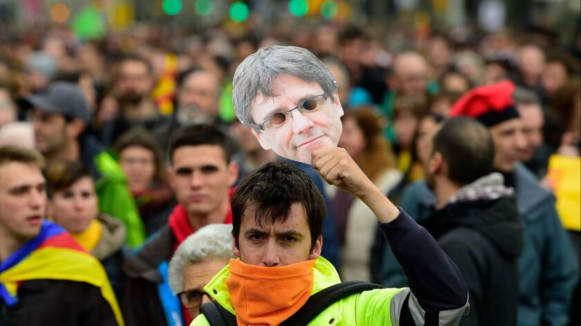 A protester holds a mask of Catalonia's former president, Carles Puigdemont, during a demonstration in Barcelona on Sunday.