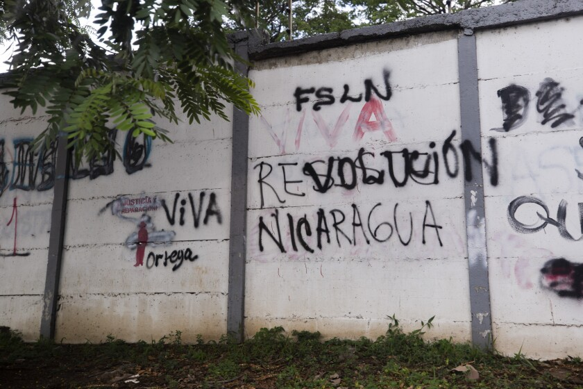 """A wall that is defaced with graffiti with one message that once read in Spanish: """"Resist Nicaragua"""", was overpainted by another that now reads """"Long live the Nicaraguan revolution"""", in Managua, Nicaragua, Thursday, June 17, 2021. In recent weeks, Nicaragua President Daniel Ortega's government has rounded up 13 opposition leaders, including four presidential challengers for the Nov. 7 elections. They face allegations ranging from money laundering to crimes against the state. (AP Photo/Miguel Andres)"""