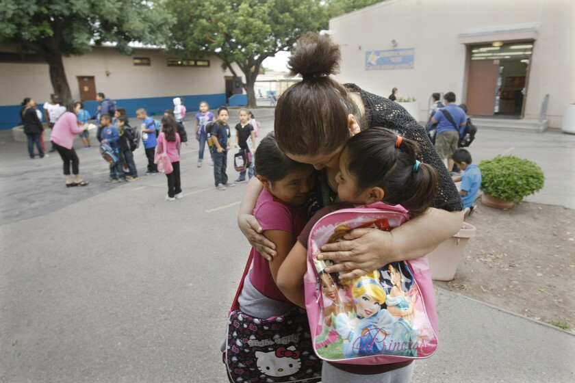Principal Irma Cobian, shown hugging two students at Weigand Avenue Elementary, had to leave the school after a group of parents petitioned for her removal. The school's faculty eventually left the school in protest.