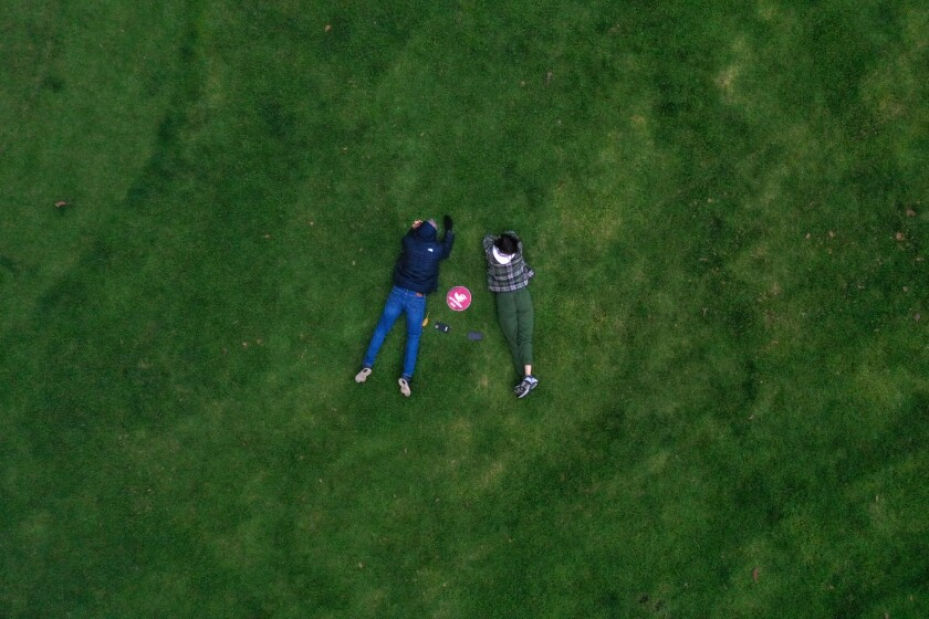 Two people lying next to each other in the grass at Holmby Park.