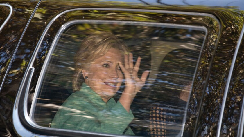 Democratic presidential candidate Hillary Clinton waves from her motorcade in Los Angeles on Aug. 23.